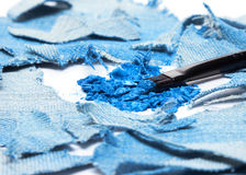 Crushed compact blue eyeshadow with rags of denim Royalty Free Stock Photo