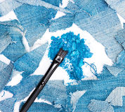 Crushed compact blue eyeshadow surrounded by rags of denim Stock Photography