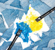 Crushed compact blue and yellow eyeshadow with rags of denim Stock Photos