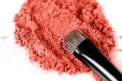 Crushed coral eye shadow and makeup brush isolated on white background royalty free stock image