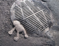 Crushed doll on manhole cover Royalty Free Stock Photos