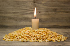 Crushed dried peas and burning candle Royalty Free Stock Photo