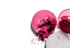 Crushed eyeshadows and lipstick isolated on white background. Beauty texture, cosmetic product and art of make-up concept - Crushed eyeshadows and lipstick royalty free stock image