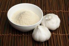 Crushed garlic powder and whole garlic Royalty Free Stock Images
