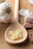 Crushed Garlic on Wooden Spoon Beside Unpeeled Cloves Stock Images