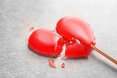 Crushed heart shaped lollipop on light background. Relationship problems Stock Photo