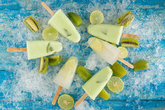 Crushed ice cubes and lemon, kiwi, homemade ice cream on vintage. Blue wooden table. Top view Royalty Free Stock Photography