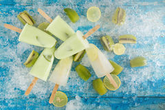 Crushed ice cubes and lemon, kiwi, homemade ice cream on vintage. Blue wooden table. Top view Royalty Free Stock Image