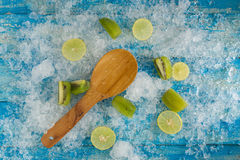 Crushed ice cubes and lemon, kiwi, wooden spoon on vintage blue Stock Photo