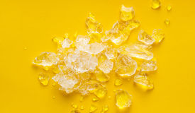 Crushed ice on vibrant yellow background Stock Photography