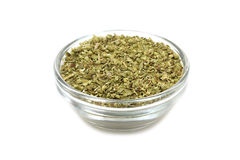 Crushed oregano leaves in a glass container Stock Photo