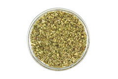 Crushed oregano leaves in a glass cup Stock Photography
