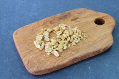 Crushed peanuts on a olive wood cutting board on a blue abstract background. Step by step cooking.. Stock Images