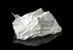 Crushed piece of paper. With reflection. Isolatein on black royalty free stock photos