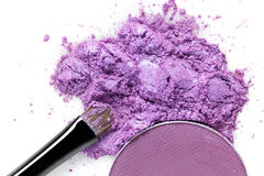 Crushed purple eye shadow and makeup brush isolated on white background Stock Photography