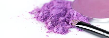 Crushed purple eye shadow and makeup brush isolated on white background Royalty Free Stock Image