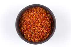 Crushed red chili pepper. In stone bowl on white background stock image