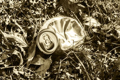 Crushed soda can lying in grass -  in sepia tone Royalty Free Stock Photos