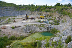 Crushed stone quarry with pond and heavy machinery Stock Photo