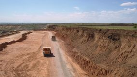 Crushed stone quarry, two trucks, aerial view