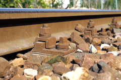 The crushed stones or ballast alongside the rail track hold the wooden cross ties in place, which in turn lock the i. The crushed stones or ballast alongside the stock photography