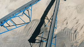 Crushed stones falling from crusher conveyor at a quarry. Rock stone crushing machine at a mining quarry.