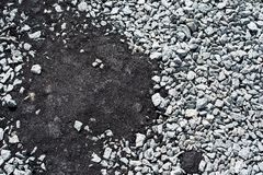 Crushed stones partly covered with new asphalt concrete Stock Images