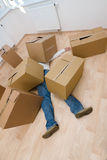 Crushed Underneath. A metaphorical image of a man crushed underneath the cardboard boxes he was carrying Stock Photo