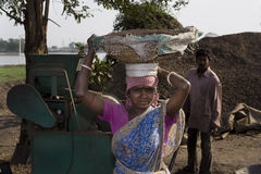 Crusher worker. A woman crusher worker is carrying a bucket full of stone in front of a crusher machine in India Stock Image