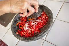 Crushing chillies Stock Images