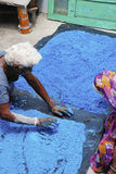 Crushing colored minerals in India. A man and woman sorting and crushing blue stones for tikka powder Royalty Free Stock Images