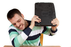Crushing my Notebook. Man trying to smash his notebook on the table Royalty Free Stock Image
