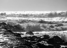 Bravery of the sea against the rocks in black and white. Crushing sea clashing against the rocks. Violent waves melt in tiny particles of water forming an Royalty Free Stock Photos
