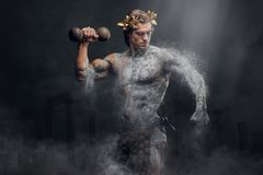 Crushing stone human athlete holds the dumbbel. Crushing stone human athlete holds the dumbbell on ancient Greek town ruins Royalty Free Stock Photography