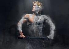 Crushing stone human athlete holds sword. Crushing stone human athlete holds sword over ancient Greek ruins Stock Image