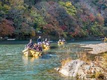 Crusing boat along river in Arashiyama. KYOTO, JAPAN - OCTOBER 24 : Crusing boat along river with colorful leaves in Arashiyama region, Kyoto, Japan Royalty Free Stock Photography