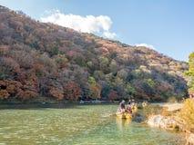 Crusing boat along river in Arashiyama. KYOTO, JAPAN - OCTOBER 24 : Crusing boat along river with colorful leaves in Arashiyama region, Kyoto, Japan Stock Images