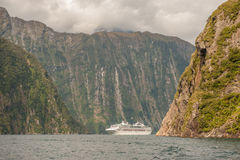 Crusing in Milford Sound, South Island, New Zealand. Milford Sound, New Zealand - February 14, 2012: Cruise ship cruising in Milford Sound. This fiord is Stock Photo