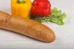 Crust baguette. With vegetables over wooden backgroind Royalty Free Stock Images