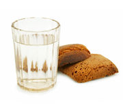 Crust of bread and glass of alcohol. Isolated on a white background Stock Photos