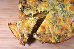 Crustless spinach quiche on a wooden board. Close-up on a sliced crustless spinach quiche on a wooden board Stock Image