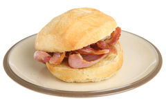 Crusty Bacon Breakfast Roll. Bacon in a crusty white bread roll or bap Stock Image