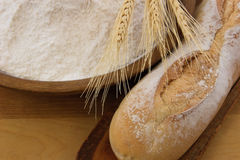 Crusty baguette bread with wooden bowl of flour Royalty Free Stock Image
