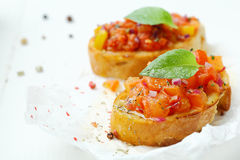Crusty baguette bruschetta on grunge paper Stock Photos