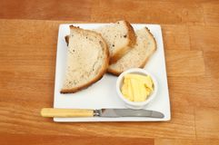 Bread and butter on a tabletop. Crusty bread and butter with a knife on a plate on a wooden tabletop Royalty Free Stock Image
