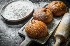 Crusty buns on a cutting Board with flour from the bowl. On black rustic background royalty free stock image