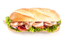 Crusty French baguette with sliced chicken. Crusty golden French baguette with sliced chicken, tomato and frilly lettuce, high angle view on a white background Stock Photo