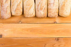 Crusty fresh bread loaf border on wood Royalty Free Stock Image