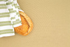 Crusty golden sesame seed loaf in a cloth Stock Photography