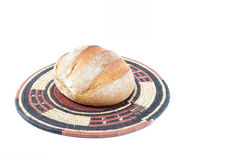 Crusty loaf of bread on a bamboo straw rustic placemat isolated Stock Photography